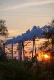 Fume de la estación de la central eléctrica de la chimenea en la puesta del sol Fotos de archivo libres de regalías