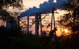 Fume de la estación de la central eléctrica de la chimenea en la puesta del sol Imagen de archivo libre de regalías