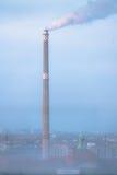 Fume de una chimenea de la fábrica en un cielo urbano nebuloso