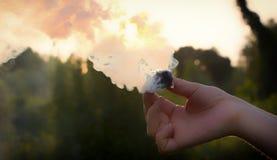 Fume o redemoinho, emita-se o fumo na mão do homem fotografia de stock