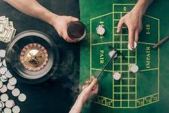 Fume sobre apuestas de colocación de la gente mientras que juega la ruleta foto de archivo libre de regalías