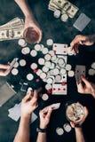 Fume sobre povos com álcool nos vidros que jogam o pôquer pela tabela do casino com dinheiro imagem de stock royalty free
