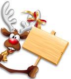 Fumetto divertente della renna di natale che tiene PA di legno Fotografia Stock