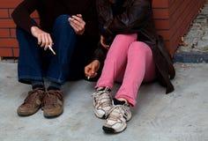 Fumeurs s'asseyant sur la terre Photographie stock libre de droits