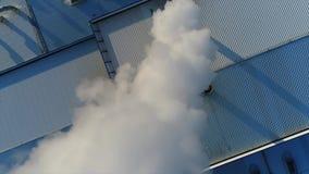 Fumez d'un tuyau sur le toit d'une usine ou de l'usine, le toit d'une salle de production avec un tuyau, fumée épaisse blanche banque de vidéos
