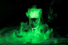 Fumez dans le verre de cocktail sur un fond noir Fond de breuvage magique de sorcière pour Halloween Boisson peu commune de barre Image stock
