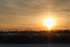 Fumez des tuyaux de l'usine dans le coucher du soleil Image stock