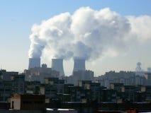 Fumi dal calore della centrale elettrica sopra la città Immagini Stock