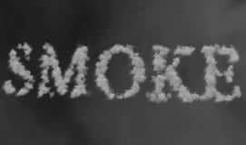 Fumi la parola fatta facendo galleggiare il vapore del fumo attraverso lo spazio sul fondo grigio della sfuocatura Immagine Stock