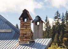 Fumi uscire nel freddo dal camino sul tetto della casa fotografie stock libere da diritti