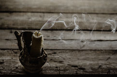 Fuming extinguished the candle on the wooden table Stock Image