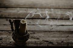 Fuming ha estinto la candela sulla tavola di legno Immagine Stock