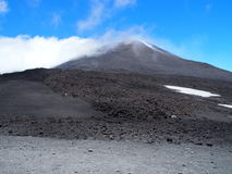Fuming Mount Etna in Sicily, Italy. Desolate fuming volcano crater, tallest active in Europe with cloudy blue sky in warm spring day: MOUNT ETNA, SICILY / ITALY Royalty Free Stock Images
