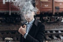Fumo alla moda dell'uomo del gangster posando sul fondo della ferrovia E Fotografie Stock