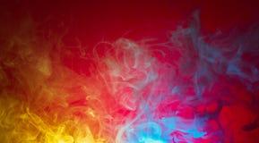 Fumo amarelo e azul no fundo vermelho Foto de Stock Royalty Free