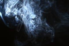 Fumo azul de fluxo maravilhoso do contraste contra o fundo preto pesado imagens de stock