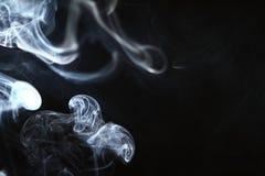 Fumo azul de incandescência de fluxo agradável contra o fundo preto pesado fotografia de stock royalty free