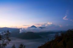 Fumo bianco che esce dai vulcani circondati dalle nuvole bianche di foschia e di chiaro cielo blu Fotografia Stock Libera da Diritti