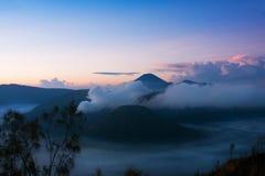 Fumo bianco che esce dai vulcani circondati dalle nuvole bianche di foschia e di chiaro cielo blu Fotografie Stock