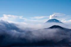Fumo bianco che esce dai vulcani circondati dalle nuvole bianche di foschia e di chiaro cielo blu Immagini Stock