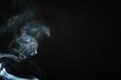 Fumo blu di mistero sopra fondo scuro con lo spazio della copia Fotografia Stock