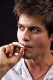 Fumo considerável novo do homem Fotografia de Stock