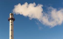 Fumo da poluição da chaminé que aumenta em um céu azul fotos de stock royalty free