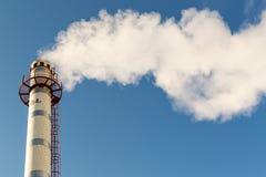 Fumo da poluição da chaminé que aumenta em um céu azul Imagens de Stock