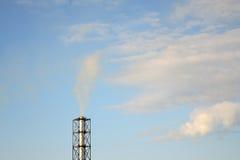 Fumo da un camino su un cielo blu immagini stock