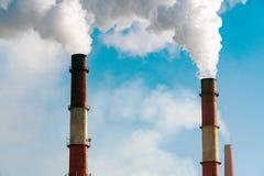 Fumo dai tubi della fabbrica contro cielo blu Fotografia Stock