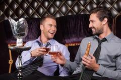 Fumo de dois homens novos da tubulação do shisha foto de stock