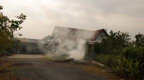 Fumo de grama ardente na frente da casa do vintage - Vietname rural foto de stock