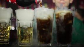 Fumo dell'azoto sui vetri di colpo alcolici variopinti sul contatore closeup HD, 1920x1080 Cocktail con azoto liquido stock footage