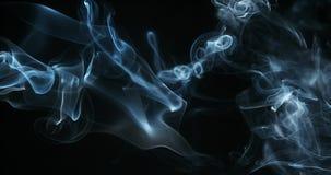 Fumo do cigarro que aumenta contra o fundo preto, filme
