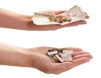 Fumo do preço Pontas de cigarro e dinheiro nas mãos foto de stock royalty free