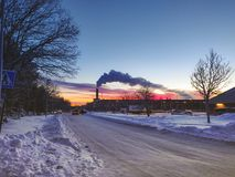 Fumo escuro no céu azul com nuvens coloridas atrás fotos de stock