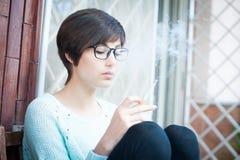 Fumo exterior, cigarro da jovem mulher viciado Imagem de Stock