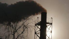 Fumo industrial de uma tubulação em uma silhueta do céu azul Fotos de Stock Royalty Free