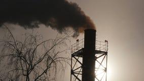 Fumo industrial de uma tubulação em uma silhueta do céu azul Imagem de Stock