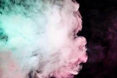 Fumo multicolore e spesso, illuminato tramite colorato alla luce verde e rosa contro un fondo isolato nero scuro, saldato con fotografia stock libera da diritti