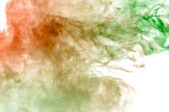 Fumo multicolorido, grosso, iluminado pelo colorido na luz verde e vermelha contra um fundo isolado branco, soldado com clubes e imagens de stock