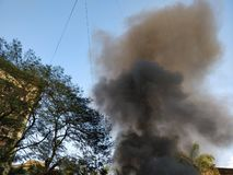 Fumo nero che esce da una costruzione sul fuoco immagine stock