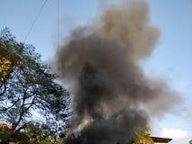 Fumo nero che esce da una costruzione sul fuoco fotografie stock