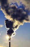 Fumo nero contro il cielo blu e la regolazione di Sun Fotografia Stock