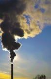 Fumo nero contro il cielo blu e la regolazione di Sun Fotografia Stock Libera da Diritti