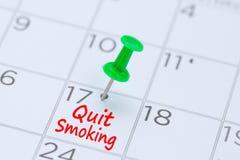 Fumo smesso scritto su un calendario con un perno verde di spinta al rem immagine stock