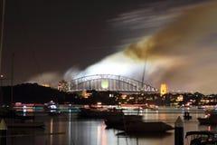 Fumo sopra il ponticello di porto di Sydney alla notte Fotografia Stock
