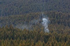 Fumo sopra la foresta in montagne fotografia stock libera da diritti
