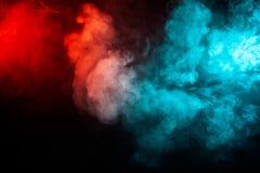 Fumo translúcido, grosso, iluminado pela luz contra um fundo escuro, dividido em duas cores: azul e vermelho, queima-se, imagem de stock