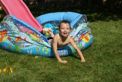 Fun. Young boy 6 years old playing in swimming pool Royalty Free Stock Image